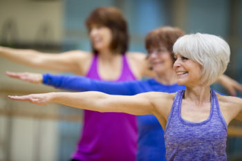 group of senior adult women are taking a yoga class